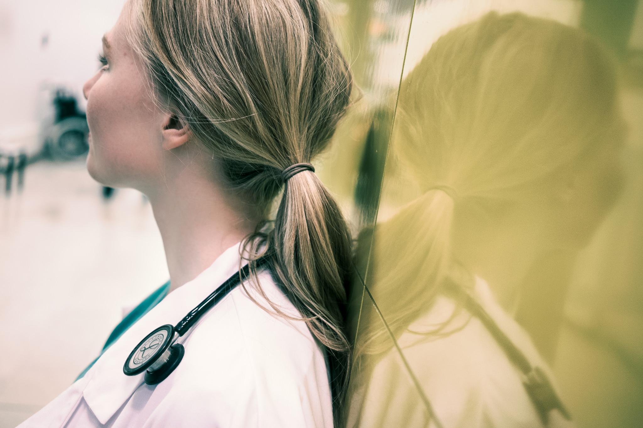 Doktor med stetoskop står på sykehus og tenker.